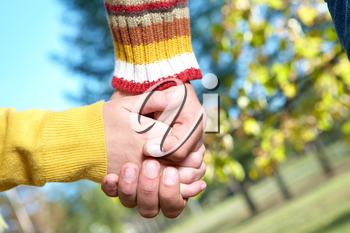 Photo of human hands holding each other outdoors