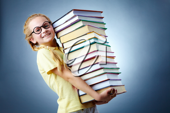 Image of happy schoolgirl with stack of books looking at camera