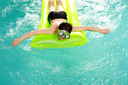 Photo of relaxed boy on matress in pool
