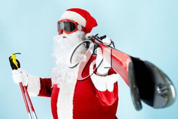 Photo of happy Santa Claus with skis looking through goggles