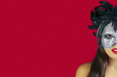 Beautiful brunette woman wearing a masqurade mask against a red background.