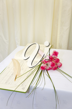 A wedding register and quill with a bouquet of pink roses on a white table.