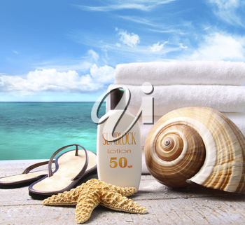 Royalty Free Photo of Sunblock, Seashells, Sandals and Towels