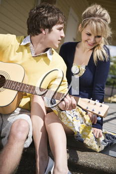 A young caucasian man playing guitar and sings to his girlfriend
