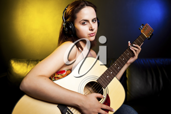 A shot of a beautiful caucasian woman wearing headphones and holding a guitar