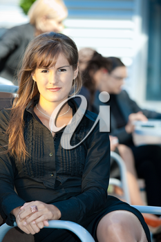 Young businesswoman sitting in chair outdoor.