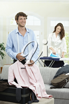 Young businessman preparing for business trip. Woman ironing in the background.