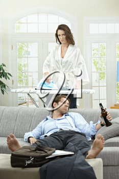 Tired businessman resting on couch with beer in hand. Angry wife ironing in the background.