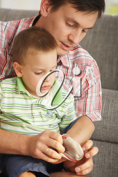 Father helping son putting on socks at home.