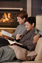 Young couple hugging on sofa in front of fireplace at home, reading books, smiling.