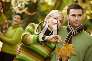 Closeup portrait of young couple embracing in autumn park, woman holding leaves.