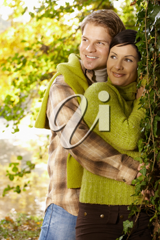 Portrait of happy young couple in autumn park standing at tree, smiling.