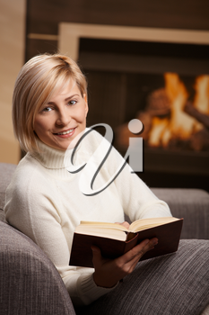 Woman sitting on sofa at home reading book, looking at camera, smiling.