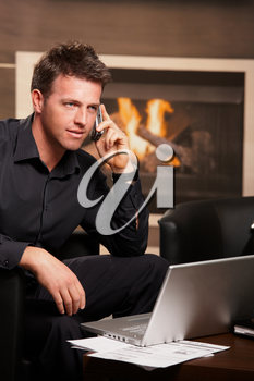 Casual businessman sitting in armchair at coffee table in front of fireplace, talking on phone.  .