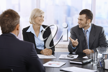 Smiling professionals sitting and talking in meeting room in skyscraper office.