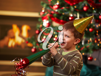 Little boy laughing on new year's eve, wearing shiny hat and blowing horn, looking at camera, christmas tree in background.
