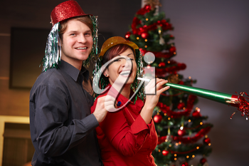 Portrait of happy couple in funny hat blowing horn on new year eve with christmas tree in background.
