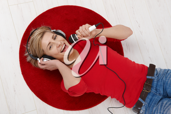 Woman lying on round red carpet of living room floor with headphones holding microphone, singing in high angle view.