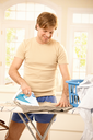 Cheerful young guy ironing clothes in bright living room.