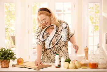 Senior woman cooking in kitchen, having vegetables and fruits around, reading recipe from book, holding egg whisk, smiling.