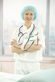 Portrait of young medical doctor standing in office, looking at camera, smiling.