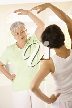Healthy senior woman doing exercises with personal trainer at home, smiling.