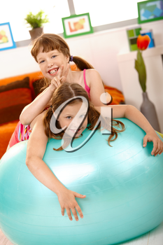 Schoolgirl teasing friend on gym ball, showing dog's-ear, laughing.