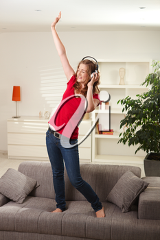 Happy teen girl listening to music on headphones dancing on couch at home with eyes closed smiling.