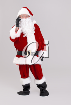 Full size portrait of Santa talking on mobile phone, looking at camera, isolated on gray background.