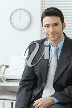 Portrait of yuong handsome businessman wearing grey suit and blue shirt sittigng on desk at office, smiling.