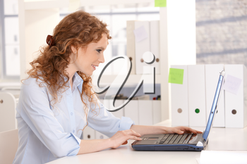 Young attractive woman using laptop browsing Internet in office.