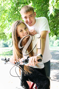 A young couple sitting on a bicycle