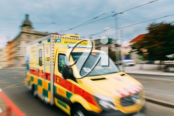 Prague, Czech Republic. Moving With Siren Bright Yellow Emergency Ambulance Reanimation Van Car On Street. Ambulance Car In Blurred Motion Background