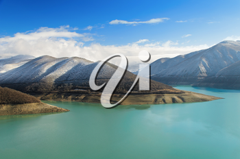 A beautiful view of Caucasus Mountains, surrounded by lake, which is an important feature of the landscape.