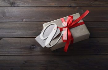 gift box with red ribbon and with a price tag on wooden table