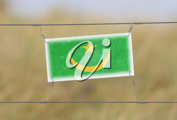 Border fence - Old plastic sign with a flag - Mauritania