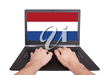 Hands working on laptop showing on the screen the flag of the Netherlands