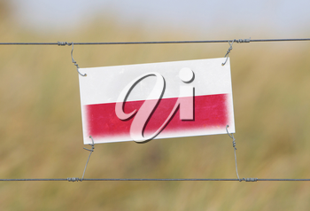 Border fence - Old plastic sign with a flag - Poland