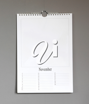 Simple old birthday calendar hanging on a grey wall, copy space - November
