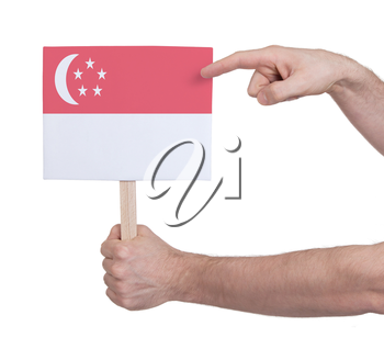 Hand holding small card, isolated on white - Flag of Singapore