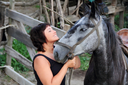 Portrait happy smiling woman with grey horse