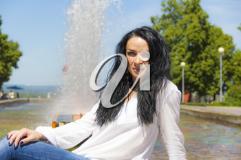 Photo of Caucasian brunette woman on fountain background