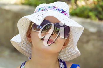 Cute girl in sunglass and white hat