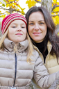 Mother and daughter on yellow foliage background