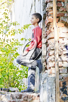 Cute boy standing near old brick wall in summer