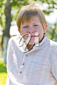 Portrait of  blond boy in a white shirt in green park