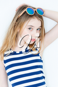 Cute blond girl eleven years old standing near white wall with green sunglasses