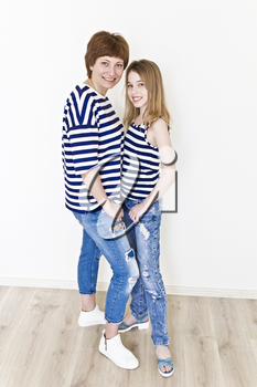 Happiest mother and daughter near white wall in striped clothes