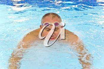 Big fat man in the swimming pool playing sports