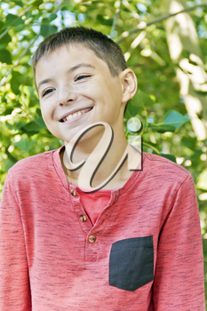 Smiling teenager boy in pink on green background